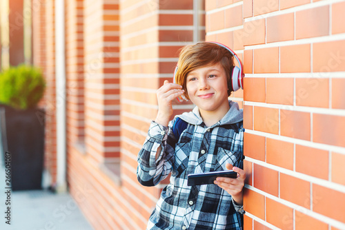 Pre-teenage boy with headphones and mobile phone listening to music