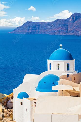 Beautiful Santorini landscape with white church, caldera, sea and sky clouds Canvas Print