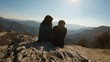 Couple sitting at a top of a mountain. View from the back
