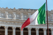 Italian Flag Fluttering In Front Of The Fatherland From Piazza Venezia In Rome, Italy, Also Known As National Monument To Victor Emmanuel II