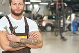 Muscular, tattoed repairman posing in autoservice.