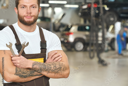 Fototapety, obrazy: Muscular, tattoed repairman posing in autoservice.