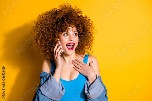 Close-up portrait of her she nice cute lovely winsome sweet charming attractive cheerful wondered stunned wavy-haired girl talking on phone isolated over bright vivid shine yellow background