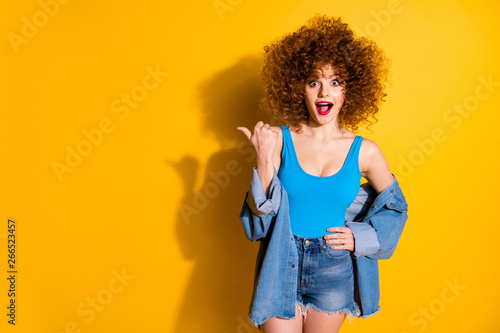 Portrait of her she nice cute lovely winsome fascinating charming attractive cheerful wondered stunned wavy-haired girl pointing aside ad advert isolated over bright vivid shine yellow background