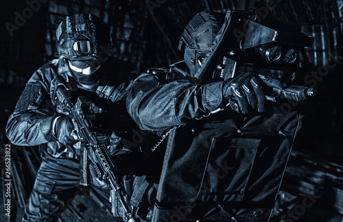 Fotografija Police SWAT unit hiding behind ballistic shield