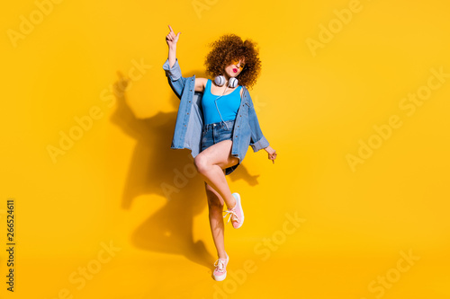 Full length body size photo funny she her lady wavy styling curls clubber sing songs hang out wear headset ear flaps specs casual jeans denim shirt shorts tank top clothes isolated yellow background
