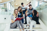 College life.Students are studying in library. Young people are spending time together. Reading book and communicating while sitting on stairs in library.