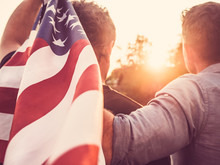 Two Friends Holding An American Flag Against A Background Of Trees And Blue Sky. View From The Back, Close-up. National Holiday Concept