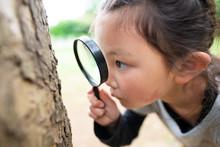 虫眼鏡を使って見る女...