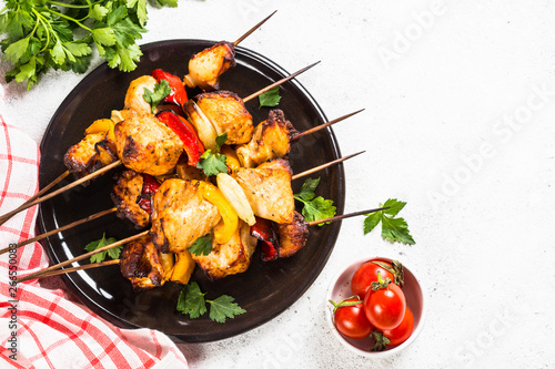 Chicken kebab with vegetables on skewers on white.