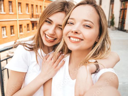 Fotografie, Obraz  Two young smiling hipster blond women in summer white t-shirt clothes