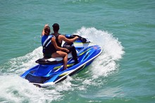 Angled Elevated View Of A Young Man And A Young Woman Riding Tandem On A Blue Jet Ski