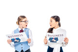 Fototapeta Panels - surprised schoolgirls in formal wear with business newspapers looking at each other Isolated On White