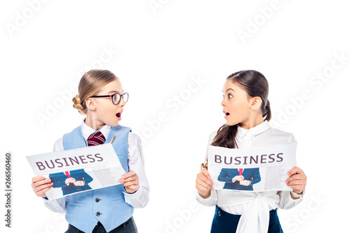 surprised schoolgirls in formal wear with business newspapers looking at each other Isolated On White
