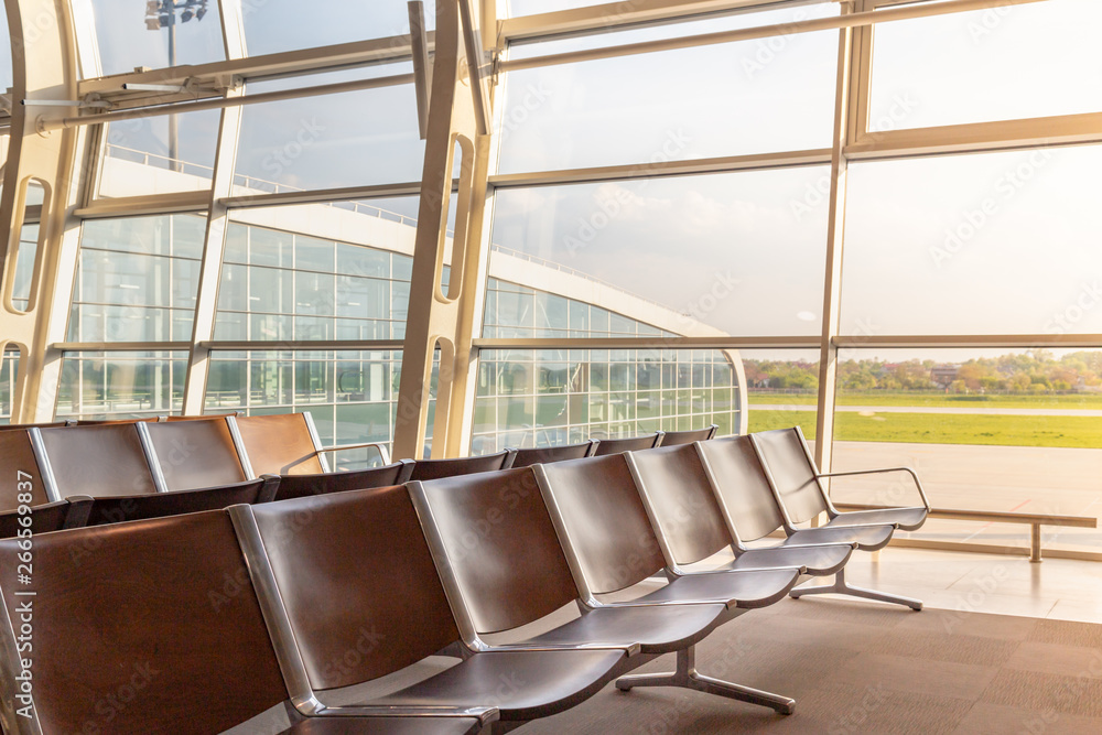 Fototapeta Ready to fly concept. Modern International airport terminal chairs lined up with a nice green scenery.
