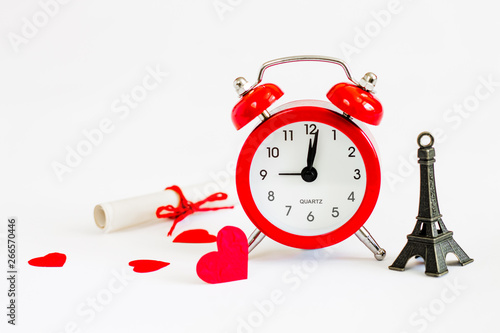Romantic trip to Paris concept. Honeymoon, time to fall in love. Invitation to a romantic trip, a love note. Eiffel tower with red alarm clock