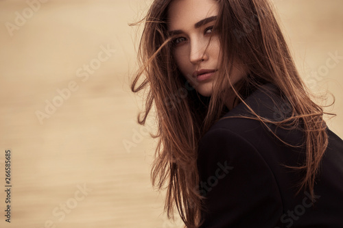 Boho style woman portrait sitting on sand, fashion clothes, sunny outdoor Wallpaper Mural
