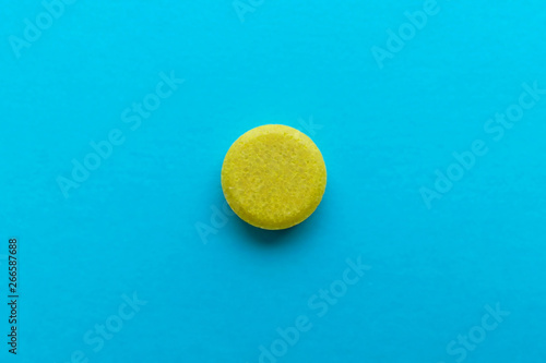 Leinwand Poster Yellow pill on blue background macro