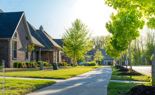 Fototapeta View of modern residential houses neighborhood street in Bentonville, Northwest Arkansas, sunny flare day, fast growing city lifestyle obraz