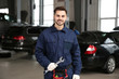 Portrait of technician with wrench at automobile repair shop