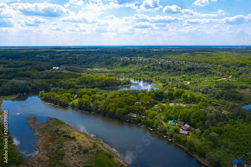 Printed kitchen splashbacks River Aerial view of river with reflected blue sky and clouds, green meadows with trees and plants. Beautiful summer nature landscape from above