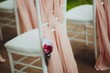 Beautiful setting for outdoors wedding ceremony. Chairs for guests of the bride and groom are decorated in the same style, decorated with fashionable fabric. chairs are placed convolution with rose