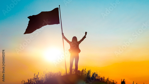 High achievement, silhouettes of the girl, flag of victory on the top of the mountain, hands up Canvas Print