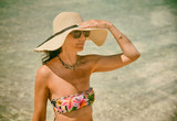 Woman wearing straw hat at ocean border touching her head. Tourism, holiday and relax concept - 266606891