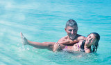 Happy family having fun in the ocean water. Young girl smiling and joking with her father. Happiness and holiday concept - 266607249