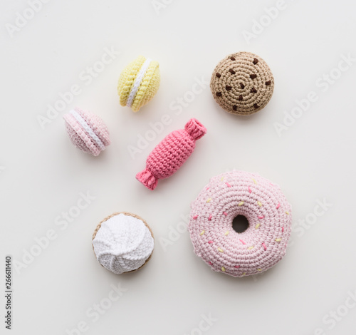 Cute knit toys for children. Cookies, macarons, candy and donut imitations on wooden background top view