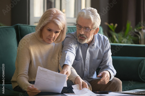 Obraz Serious grey haired mature couple calculating bills, checking finances together - fototapety do salonu