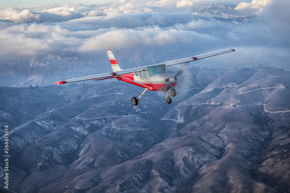 Fototapety, obrazy: Small single engine airplane flying in the gorgeous sunset sky through the sea of clouds above the spectacular mountains