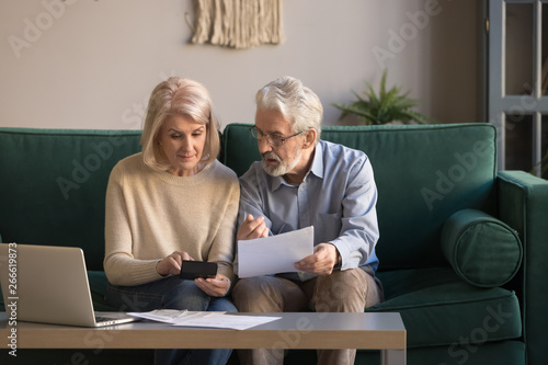 Fotografía  Serious mature couple calculating bills, checking domestic finances