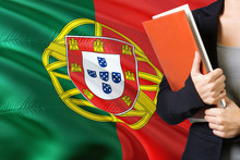 Learning Portuguese Language Concept. Young Woman Standing With The Portugal Flag In The Background. Teacher Holding Books, Orange Blank Book Cover.