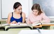 Leinwandbild Motiv Smiling schoolgirls are learning at the desk