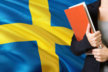 Learning Swedish Language Concept. Young Woman Standing With The Sweden Flag In The Background. Teacher Holding Books, Orange Blank Book Cover.