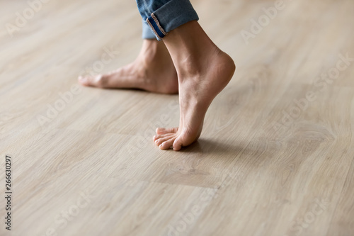 Fototapeta  Side closeup view woman feet stands on warm wooden floor