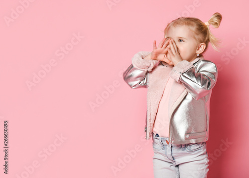 Valokuva  Portrait of a little girl in stylish clothing sitting on pink background and pla