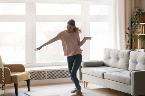 Full-length of active young woman dancing in living room - 266630638