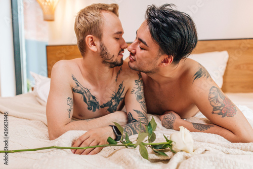 Fotomural  Gay couple waking up in the morning lying under a blanket in bed kissing each ot