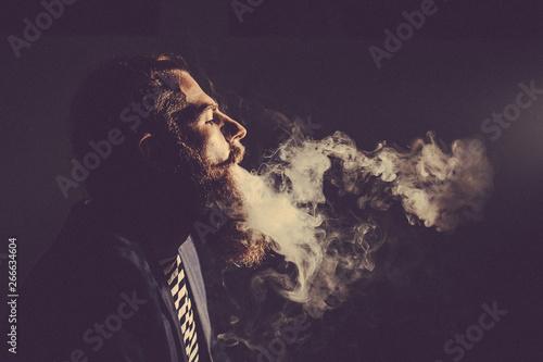 Spoed Foto op Canvas Aquarel Gezicht bearded man smoking a hookah in a dark room. Toned image