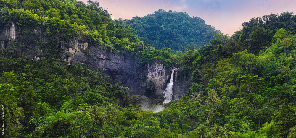 Fototapeta Wonderful Landscape of Cascade Waterfall in Tropical Rainforest. Scenery of Rocky Cliff and Cimarinjung Waterfall at UNESCO Global Geopark Ciletuh.