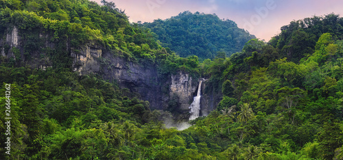 Wonderful Landscape of Cascade Waterfall in Tropical Rainforest. Scenery of Rocky Cliff and Cimarinjung Waterfall at UNESCO Global Geopark Ciletuh. - 266641262
