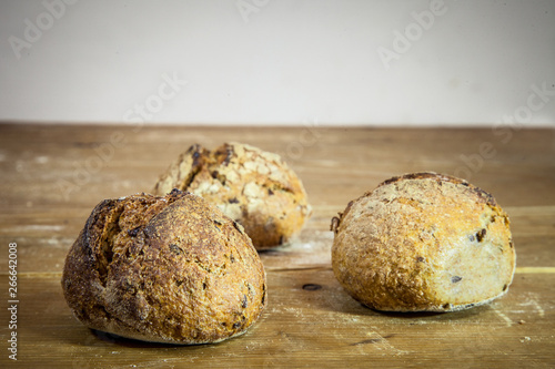 Fotografía  Three small loafs of French bread on display on a rustic wooden table, baguette style