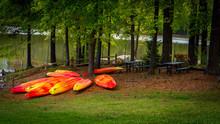 Orange And Yellow Kayaks Stored Upside Down