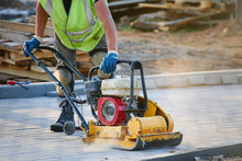 Worker In Uniform And Knee Pads Use Vibratory Plate Compactor For Path Construction. Plate Compactor For Compaction Soil Or Pavement Or Sidewalk. Indastrial Equipment. Laying And Tamping Paving Slabs