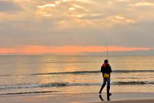 夕焼けに染まる材木座で釣りをする人