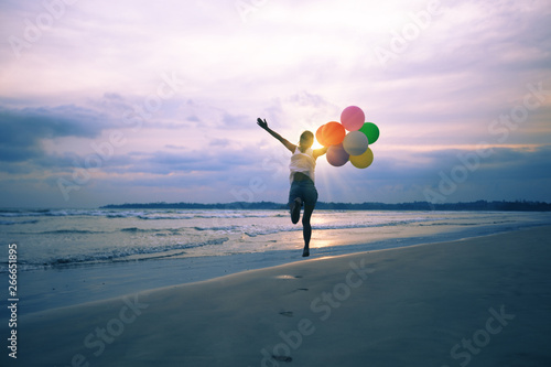Photo  young asian woman running and jumping on seaside with colored balloons