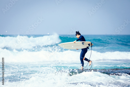 Woman surfer with surfboard going to surf the big waves - 266652019