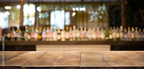 Cadres-photo bureau Alcool Defocused background and bottles of restaurant, bar or cafeteria background. Wooden table top for product display.